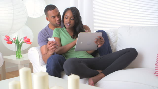 Black couple sharing information on their devices