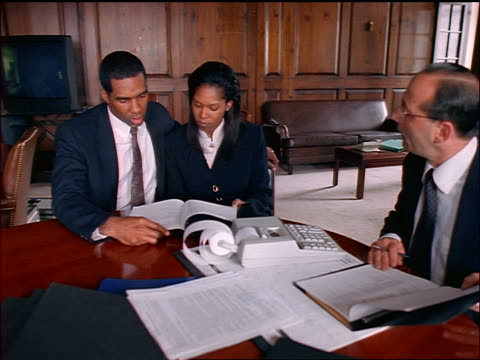 Black couple sits at table with male financial advisor/lawyer / he gives them papers + they sign