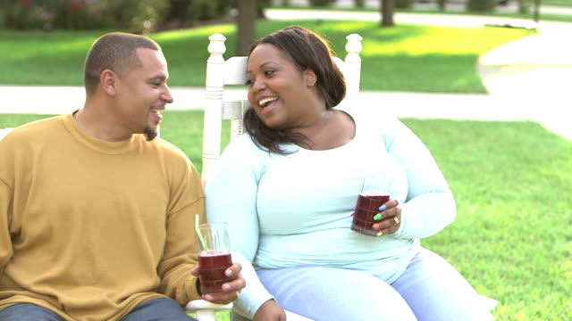 black couple sitting outdoors, drinking refreshments - body positive stock videos and b-roll footage