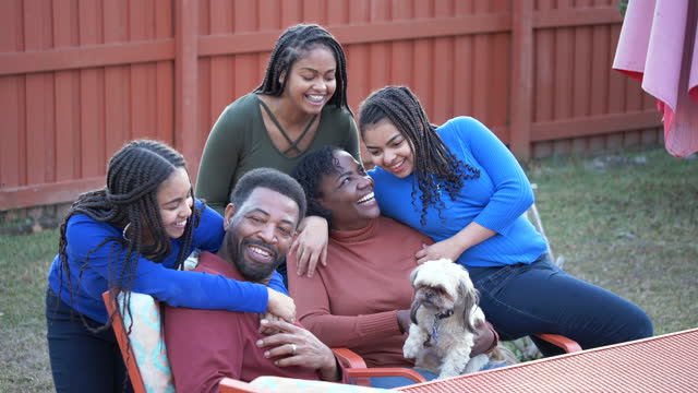 black couple sitting, teen daughters run up from behind - 55 59 years stock videos & royalty-free footage