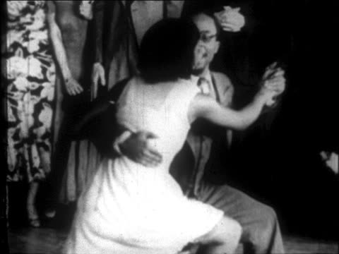 vidéos et rushes de b/w 1927 black couple squatting + dancing lindy hop on floor in harlem nightclub / nyc / newsreel - rock