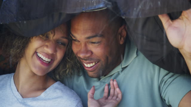 black couple standing under coat trying not to get wet - coat stock videos & royalty-free footage