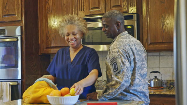 Black couple talking in kitchen after work with woman unloading groceries