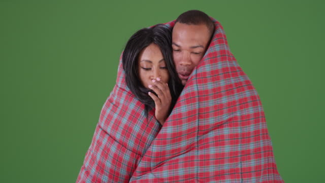 black couple wrapped up in sleeping bag while camping on green screen - 寝袋点の映像素材/bロール