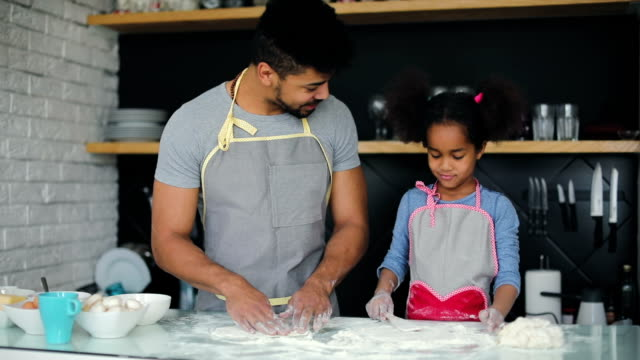 Black dad and young daughter making pizza