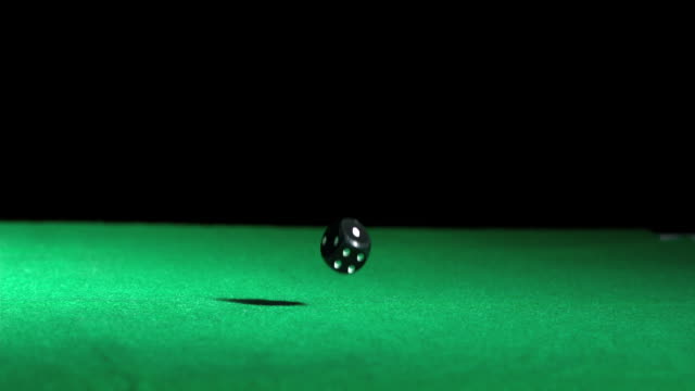 Black dice falling and bouncing on green table