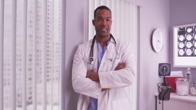 vídeos de stock, filmes e b-roll de black doctor smiling at camera - paramédico