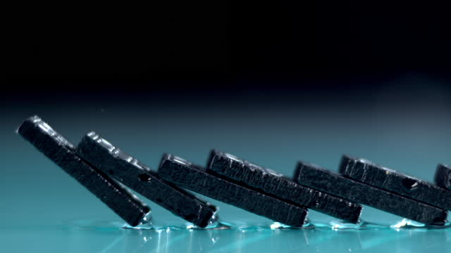 slo mo ts black dominoes falling in a chain reaction - slow-motion stock videos & royalty-free footage