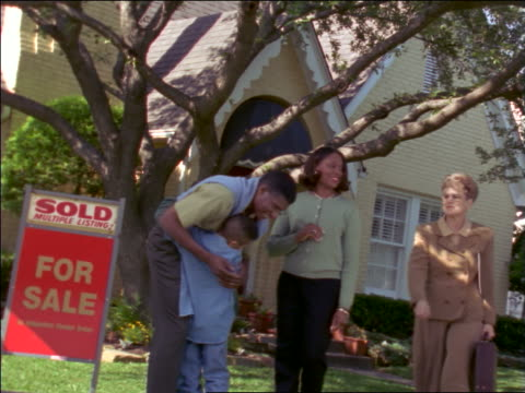 """black family hugging outside house for sale with """"sold"""" sign as real estate agent talks to them - estate agent sign stock videos & royalty-free footage"""