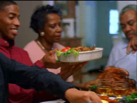 pan black family passing food around holiday table / woman serving food to girl / thanksgiving - thanksgiving stock videos and b-roll footage