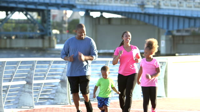 Black family with two children exercising, power walking