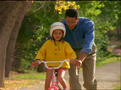black father helping daughter wearing helmet ride small bicycle toward camera - sports helmet stock videos & royalty-free footage