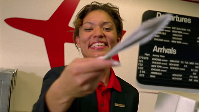 MS Black female airline ticket agent smiling + handing ticket towards camera at check in desk / AZ