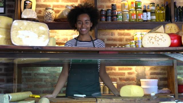 vídeos de stock, filmes e b-roll de negra dona de uma lanchonete atrás da geladeira sorrindo para a câmera - feirante