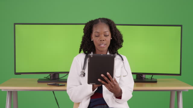black female doctor using tablet on greenscreen, computer screens in background - {{asset.href}} stock videos & royalty-free footage