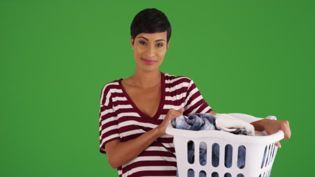 black female holding laundry basket, laughing at camera on green screen - laundry basket stock videos and b-roll footage