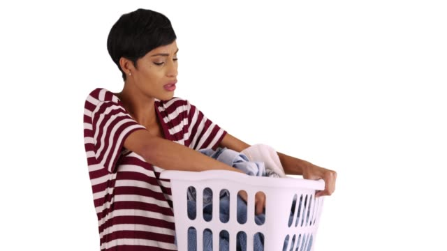 black female holding laundry basket looking through dirty clothes in studio - detersivo per bucato video stock e b–roll