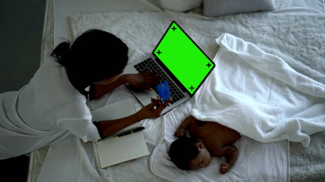 black female holding visa credit card while using laptop computer online shopping with green screen monitor during newborn baby sleeping - black computer monitor stock videos & royalty-free footage