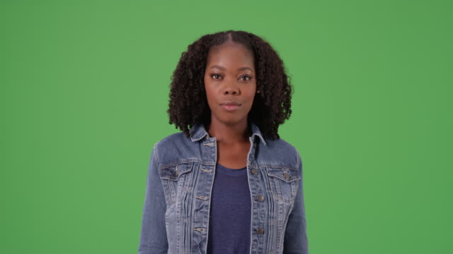 black female in cute denim jacket looking directly at camera on green screen - denim jacket stock videos and b-roll footage