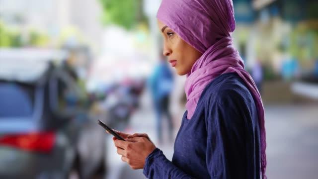 vídeos de stock, filmes e b-roll de black female in her 20s wearing hijab, texting on cellphone on urban street - smart