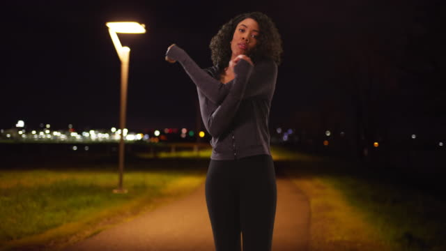 stockvideo's en b-roll-footage met black female jogger looking at camera, warming up before nightly run outdoors - jogster