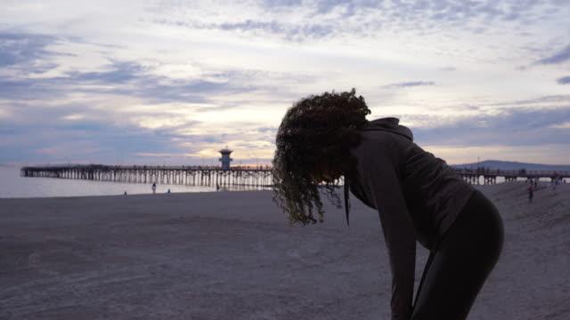 black female jogger taking a breath after run on pretty shore at dusk - resting点の映像素材/bロール