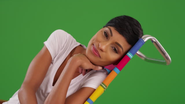 black female lounging, looking at camera with joyful smile on green screen - zurücklehnen stock-videos und b-roll-filmmaterial