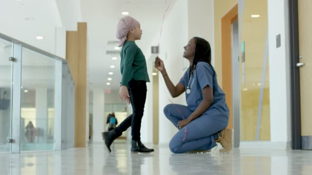 black female nurse giving balloon to child cancer patient - female nurse stock videos & royalty-free footage