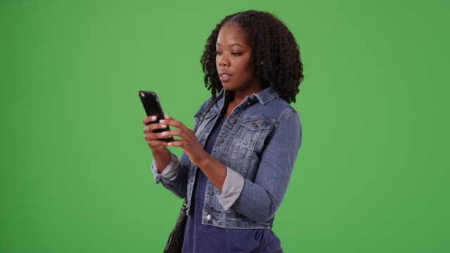 black female smiles at cute text message from boyfriend on green screen - denim jacket stock videos & royalty-free footage
