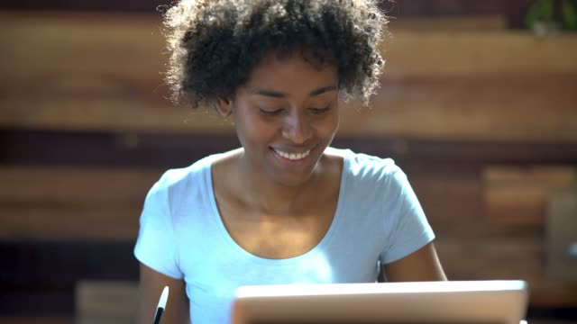 Black female student using a laptop and a notepad smiling while studying at home