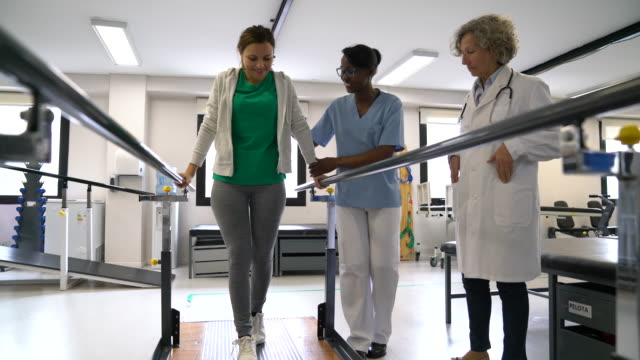 black female therapist motivating female patient walk with the help of parallel bars and senior orthopedist observing next to them - effort stock videos & royalty-free footage