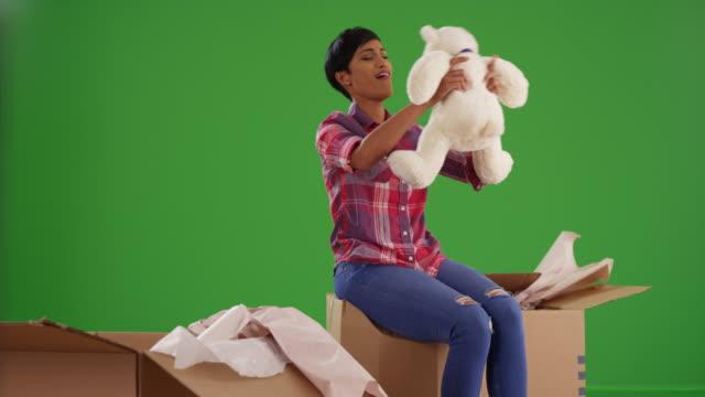 stockvideo's en b-roll-footage met black female unpacking box in new home, excited to find teddy bear on green screen - teddybeer