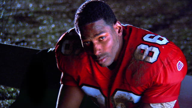 ms portrait black football player sitting on bench raising head to camera at night - only men stock videos & royalty-free footage