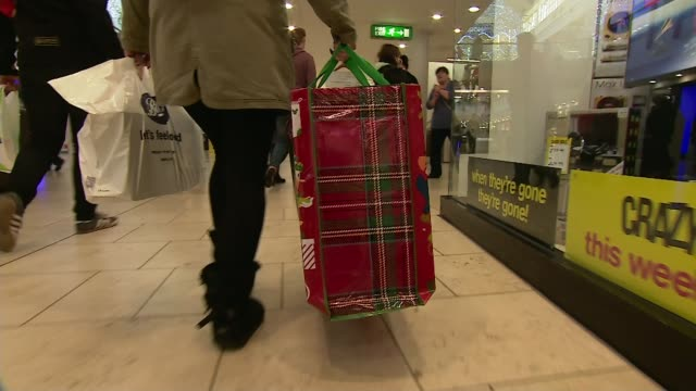 most shopping done online location unknown people along in shopping centre woman carrying shopping bags london ext pete moorey interview sot location... - black friday stock videos & royalty-free footage