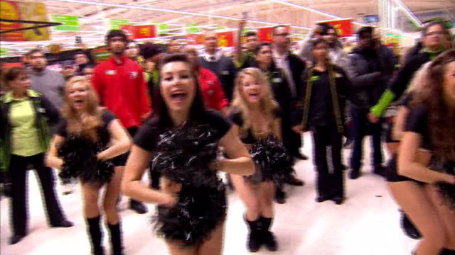 mayhem at some stores cheerleaders leading cheer in asda store sot a s d a - black friday stock videos & royalty-free footage