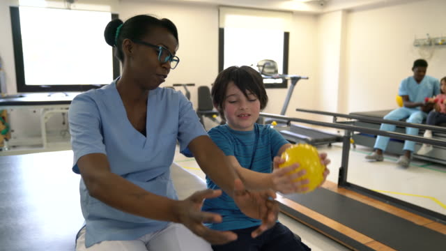black friendly therapist explaining the exercise to little boy while he follows her with a ball at physical therapy - physical therapy stock videos & royalty-free footage