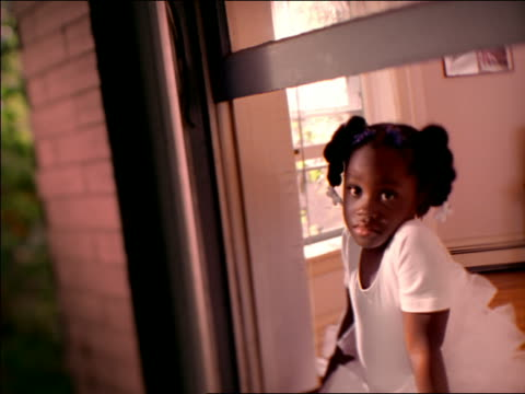 canted soft focus portrait black girl in tutu leaning out open window, turning to camera + smiling - tutu stock videos & royalty-free footage