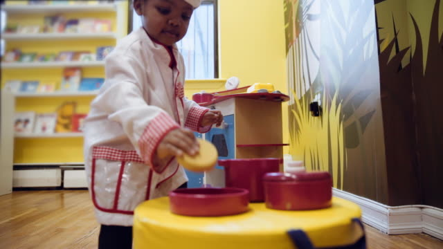 black girl playing in toy kitchen at daycare - barnomsorg bildbanksvideor och videomaterial från bakom kulisserna