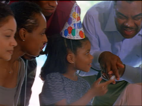 canted pan black girl putting frosting on senior man's nose as family laughs at birthday party - two parents stock videos & royalty-free footage