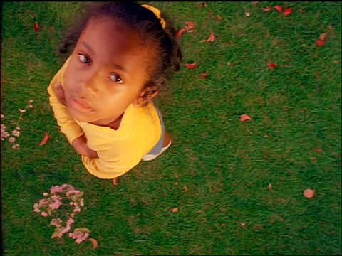 OVERHEAD Black girl standing on grass with arms folded pouting + shaking head
