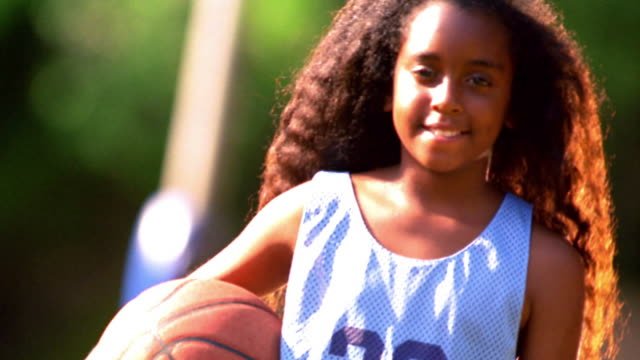 vídeos y material grabado en eventos de stock de canted ms portrait black girl wearing basketball uniform + holding basketball outdoors / florida - uniforme