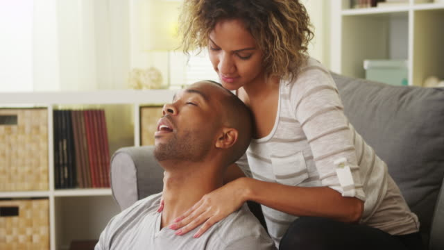 vídeos y material grabado en eventos de stock de black girlfriend giving boyfriend neck massage - massage room