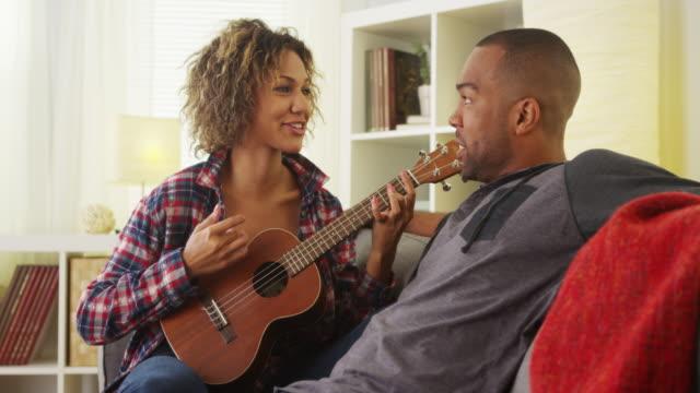 Black girlfriend serenading her boyfriend with ukulele