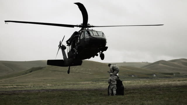 black hawk approaching cargo and soldiers attaching the hoist line. - black hawk helicopter stock videos and b-roll footage