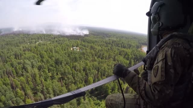 black hawk helicopter from the alaska army national guard flies over and drop buckets of water on hotspots in an effort to control montanna creek fire - black hawk helicopter stock videos and b-roll footage
