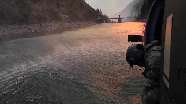 black hawk helicopter from the california army national guard fly over and drop buckets of water on the camp fire, california, as it burns in the... - evacuazione video stock e b–roll