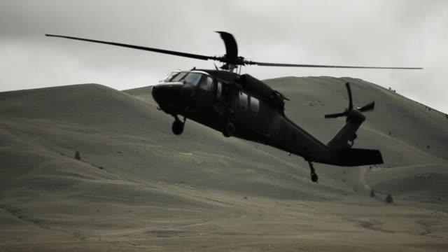 Black hawk helicopter lowering to land