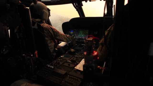 black hawk helicopters from the california army national guard fly over and drop buckets of water on the camp fire california nov 14 2018 - black hawk helicopter stock videos and b-roll footage