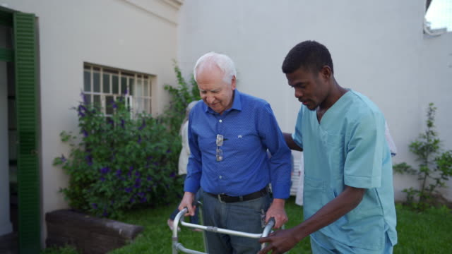 black healthcare worker helping senior man with mobility walker outdoor - the ageing process stock videos & royalty-free footage