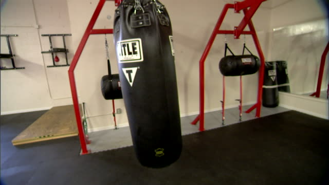 stockvideo's en b-roll-footage met black heavy bag punching bag swinging slightly from red beam in unidentifiable gym boxing training punching boxer sports work out power - stootzak fitnessapparatuur